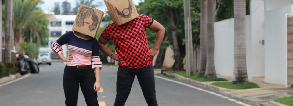 man and woman holding brown cardboard box walking on the street during daytime